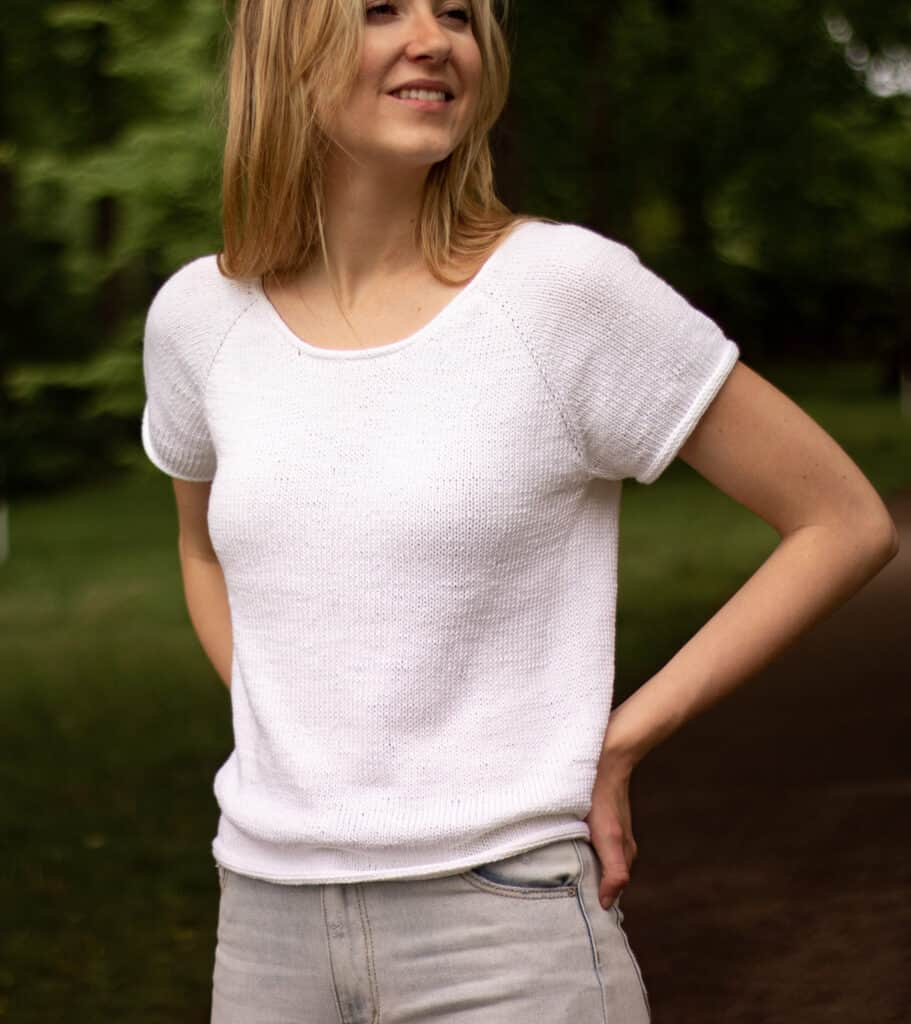 Strick-T-Shirt Detailbild mit Ausschnitt am Modell mit den Händen auf den Hüften