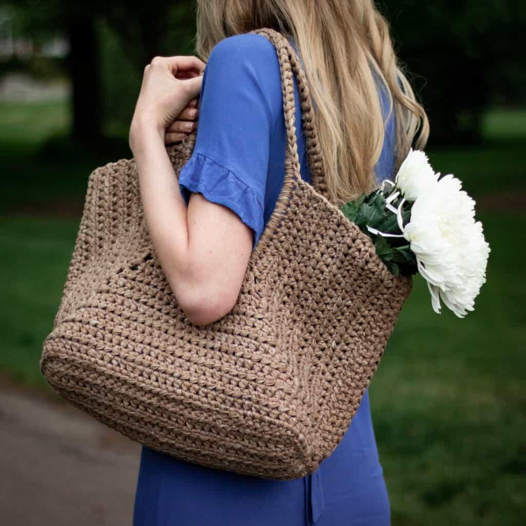 Detailaufnahme einer Einkaufstasche mit Nähten, die sie wie einen Korb aussehen lassen.  Weiße Blumen werden drinnen gehalten