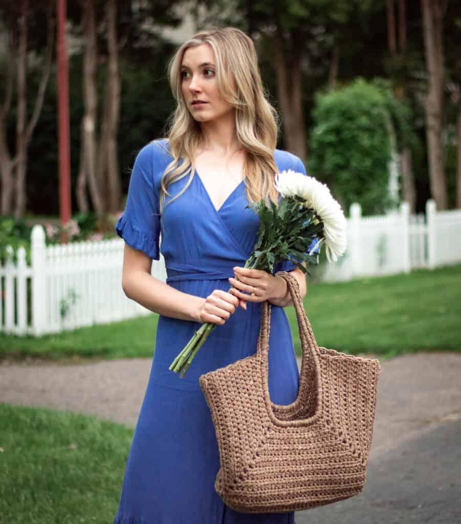 Frau im blauen Kleid, das zur Seite schaut, mit einer Tasche, die an ihrer Seite gehalten wird.  Sie steht vor einem weißen Zaun mit weißen Blumen und es ist Sommer