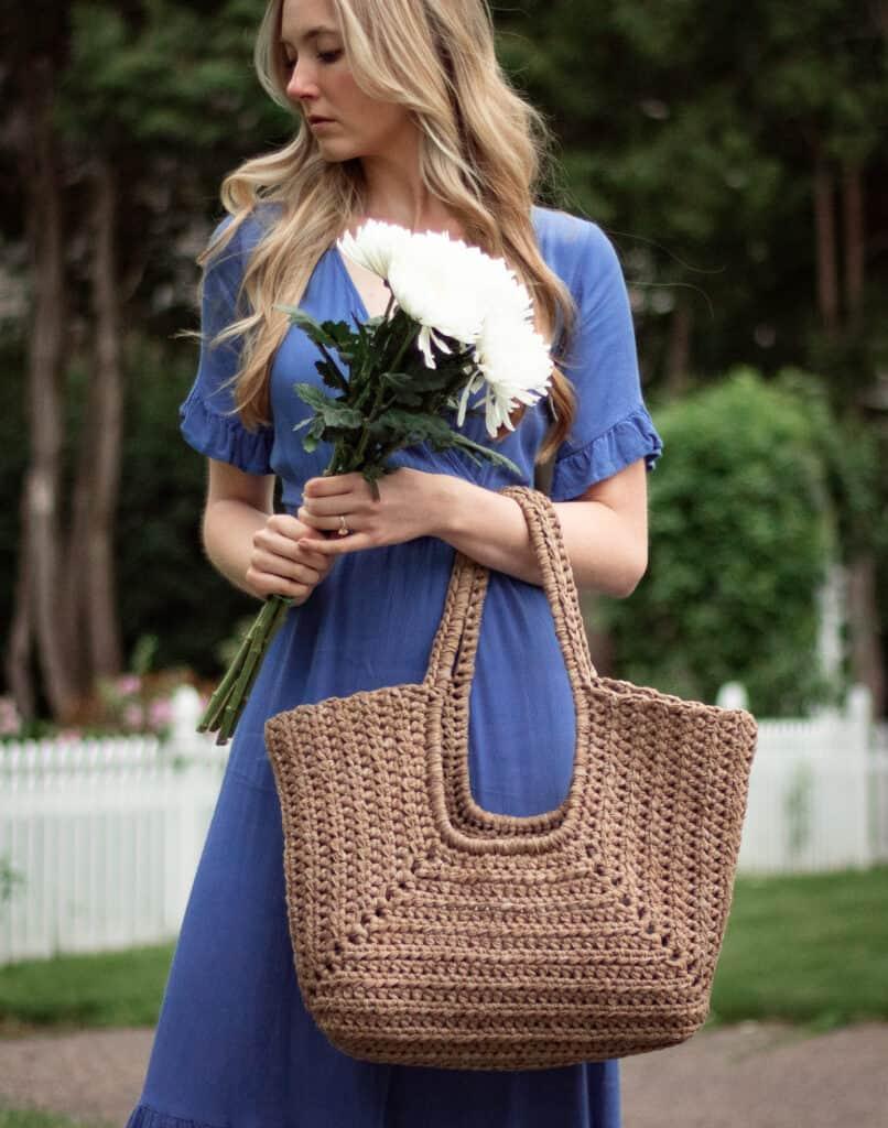 Frau mit Blumen und einer strukturierten Häkeltasche auf ihrem Unterarm.  Sie trägt ein blaues Kleid und steht vor einem weißen Zaun