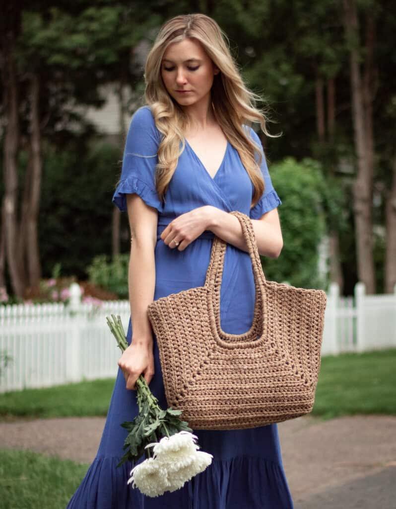 Frau mit einer Handtasche und einem Blumenstrauß, der Wind durch ihr Haar weht