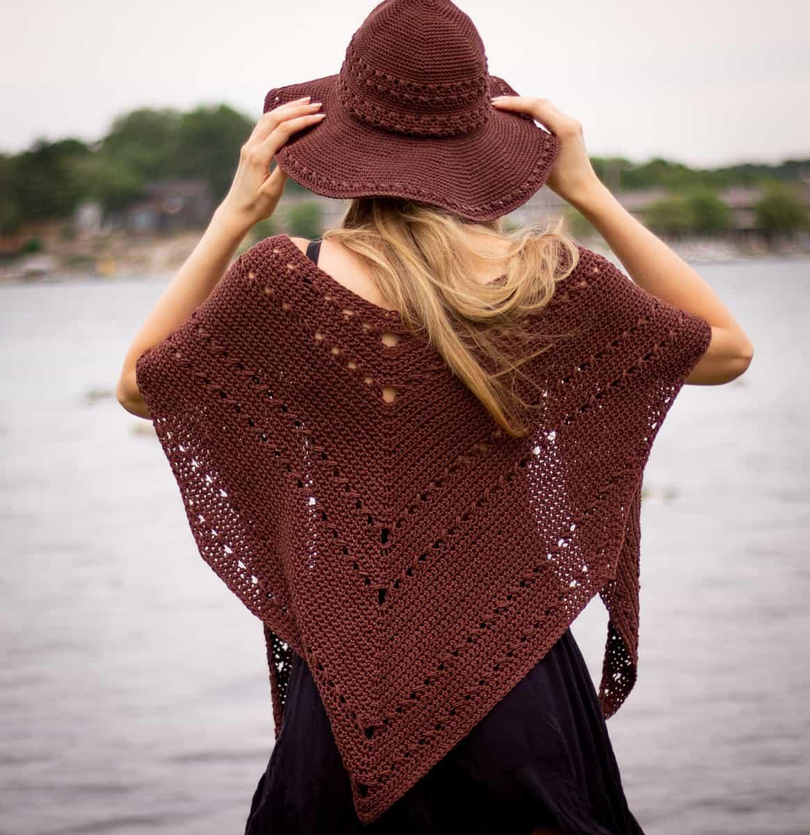 Seaside Schal wird mit dem Seaside Sonnenhut vor Wasser getragen.  Model trägt den Schal im traditionellen Stil über den Schultern.  Dieser Schal ist wandelbar und dies ist nur eine von vielen Möglichkeiten, ihn zu tragen