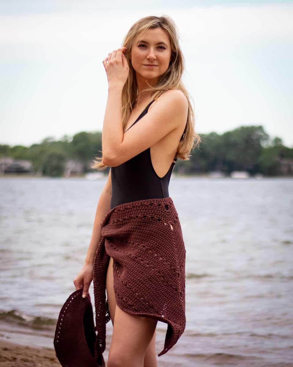 Seaside wandelbares Häkeltuch, das als Badeanzug-Vertuschung am Strand getragen wird.  Model hält den Sonnenhut am Meer an ihrer Seite