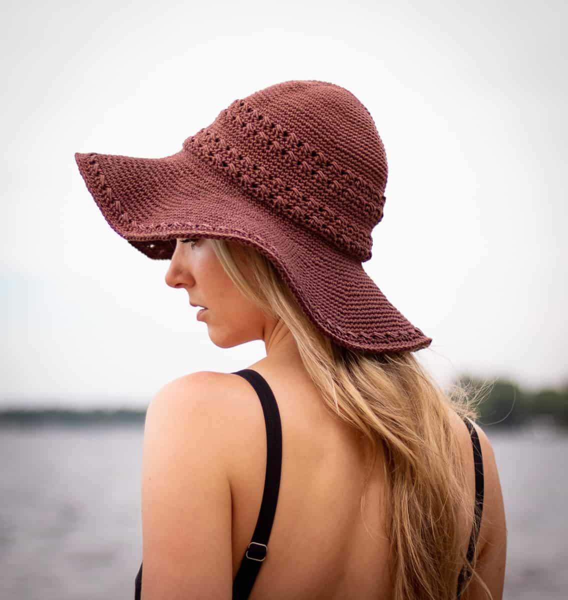 Seaside Sun Hat Häkelmuster Hauptbild zeigt ein Modell, das den Hut an einem Strand trägt und zur Seite schaut, um die Details des Hutes anzuzeigen