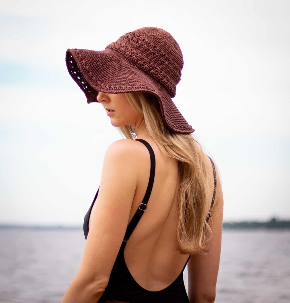 Seaside Sonnenhut Häkelmuster, das vom Modell im Badeanzug getragen wird und die leichte Floppy-Natur des Hutes zeigt und wie es das Gesicht vor der Sonne schützt