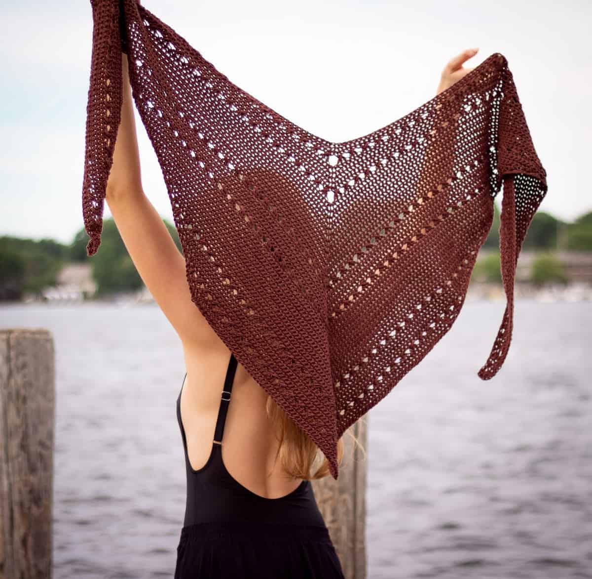 Das Hauptbild des Seaside-Schals zeigt den Schal, der in die Luft gehalten wird, um die einzigartig verjüngte Dreiecksform zu zeigen, die auf viele Arten getragen werden kann